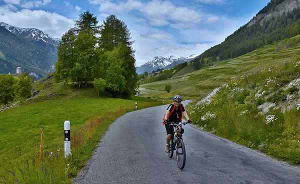 CH-RHEIN Swiss Alps-view on the cyclist on the mountain road above Ardez 183056288