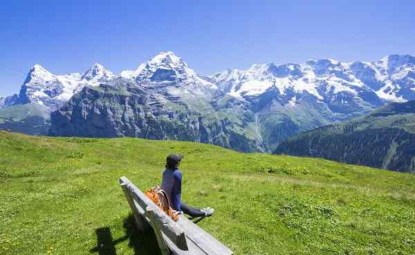 CH-SEEN-ROUTE Traveler siting on the wooden bench looking to beautiful mountain view  Murren  Switzerland shutterstock 495173056