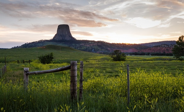 HARLEY-WILD-WEST sunset including a farm and Devils Tower National monument   old west concept shutterstock 217948048