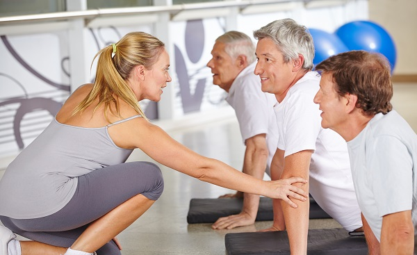 RUECKEN-SCHLIE Fitness instructor helping senior people in gym during back training class shutterstock 319960019