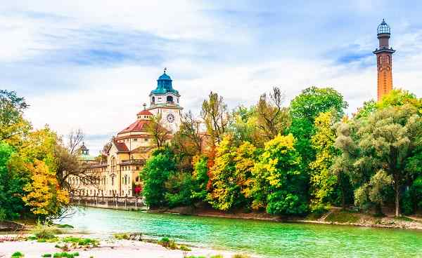 View on Colorful autumn landscape in front of Mueller Volksbad of Isar river - Munich shutterstock 1171899118